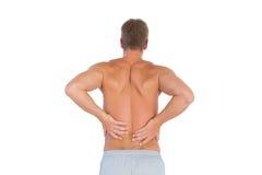 Hombre descamisado que sufre de un dolor más de espalda Imágenes de archivo libres de regalías