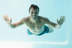 Hombre descamisado sonriente que nada bajo el agua Fotografía de archivo