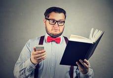 Hombre desconcertado confundido con el libro y el teléfono Fotografía de archivo libre de regalías