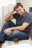 Hombre desconcertado que ensambla los muebles del paquete plano Fotos de archivo