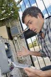 Hombre desconcertado que intenta reparar el dispositivo eléctrico Foto de archivo