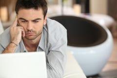Hombre desconcertado que se sienta en la computadora portátil Foto de archivo