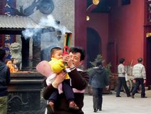Hombre desconocido con un niño que sostiene los palillos de ídolo chino en el templo de dios de la ciudad Fotografía de archivo