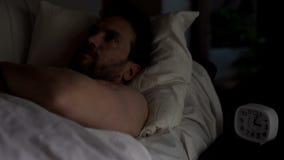 Hombre descontentado que miente en la cama incapaz de caer dormido, mirando el techo, insomnio fotos de archivo