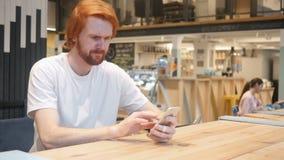 Hombre descontentado que usa Smartphone en el café, trastorno por problemas metrajes