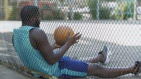 Hombre descontentado solo que se sienta en la cancha de básquet y que sostiene la bola, depresión metrajes