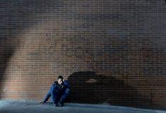 Hombre desempleado desesperado joven que el trabajo perdido perdió en la depresión que se sentaba en la esquina de calle de tierr Imágenes de archivo libres de regalías