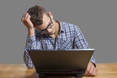 Hombre desesperado que se sienta en el ordenador imagenes de archivo