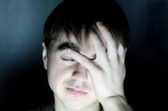 Hombre desesperado que sostiene el retrato principal del dolor de cabeza de la sensación en el ambiente oscuro, cara seria que pi Fotografía de archivo