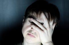 Hombre desesperado que sostiene el retrato principal del dolor de cabeza de la sensación en el ambiente oscuro, cara seria que pi Foto de archivo