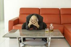 Hombre desesperado y deprimido con el traje negro que pasa tiempo con la botella de whisky Foto de archivo