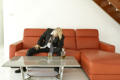 Hombre desesperado y deprimido con el traje negro que pasa tiempo con la botella de whisky Imagen de archivo libre de regalías