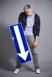 Hombre desgraciado que lleva a cabo la muestra de la flecha de la dirección que señala abajo. Imagen de archivo