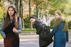 Hombre desleal que camina con la novia y que mira sorprendido otra muchacha atractiva Imagen de archivo libre de regalías