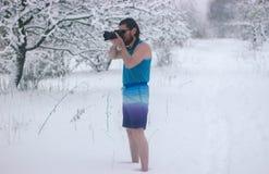 Hombre desnudo con el soporte de la cámara en el bosque del invierno Foto de archivo