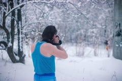 Hombre desnudo con el soporte de la cámara en el bosque del invierno Fotos de archivo