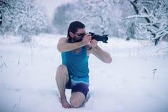Hombre desnudo con el soporte de la cámara en el bosque del invierno Fotografía de archivo
