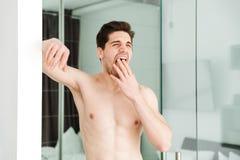 Hombre desnudo de bostezo soñoliento que se coloca en hogar fotos de archivo