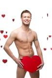 Hombre desnudo divertido que lleva a cabo el corazón de papel rojo grande Foto de archivo