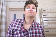 Hombre despertado soñoliento con una resaca con los remiendos de los ojos en el cuarto de baño imagen de archivo libre de regalías