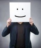 Hombre detrás del símbolo sonriente Imagenes de archivo