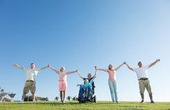 Hombre discapacitado con la familia afuera Fotografía de archivo