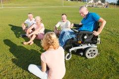 Hombre discapacitado con la familia afuera Fotografía de archivo libre de regalías