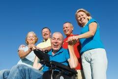 Hombre discapacitado con la familia afuera Imagen de archivo libre de regalías
