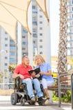 Hombre discapacitado con su fiilng de la esposa feliz mientras que lee la Sagrada Biblia Imagenes de archivo