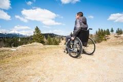 Hombre discapacitado del ofYoung granangular de la foto en silla de ruedas afuera en naturaleza observando las montañas y la natu foto de archivo libre de regalías