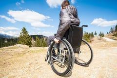 Hombre discapacitado del ofYoung granangular de la foto en silla de ruedas afuera en naturaleza observando las monta?as y la natu fotos de archivo libres de regalías