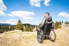 Hombre discapacitado del ofYoung granangular de la foto en silla de ruedas afuera en naturaleza observando las monta?as y la natu foto de archivo