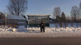 Hombre discapacitado en el autobús que espera de la silla de ruedas para en invierno metrajes