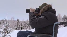 Hombre discapacitado en la silla de ruedas con la cámara profesional de la foto en bosque metrajes