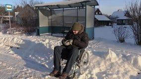 Hombre discapacitado en la silla de ruedas con la tableta que comprueba las rutas de autobús almacen de metraje de vídeo