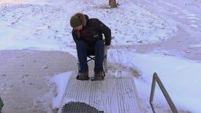 Hombre discapacitado en la silla de ruedas que intenta conducir a la entrada almacen de metraje de vídeo