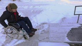 Hombre discapacitado en la silla de ruedas que intenta conducir a la puerta de entrada almacen de metraje de vídeo
