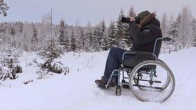 Hombre discapacitado en la silla de ruedas usando cámara profesional de la foto en invierno almacen de metraje de vídeo