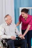 Hombre discapacitado en la silla de ruedas y la enfermera Foto de archivo libre de regalías