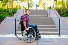 Hombre discapacitado en silla de ruedas delante de las escaleras fotos de archivo libres de regalías