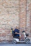 Hombre discapacitado en un mini coche delante de una pared de ladrillo Imagen de archivo