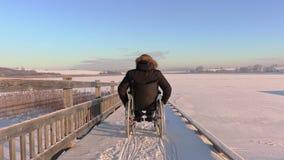 Hombre discapacitado feliz en la silla de ruedas cerca del lago en invierno almacen de metraje de vídeo