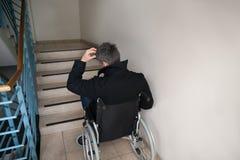 Hombre discapacitado preocupante delante de la escalera Fotografía de archivo libre de regalías