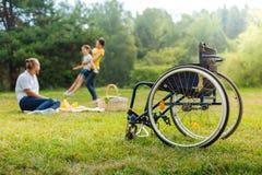 Hombre discapacitado que mira a su hija de la vuelta de la esposa imagenes de archivo