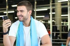 Hombre distraído con el teléfono móvil en el gimnasio fotografía de archivo