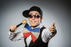 Hombre divertido con el mic en concepto del Karaoke Foto de archivo