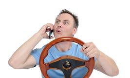 Hombre divertido con el volante que habla en el teléfono, aislado en el fondo blanco Imagen de archivo