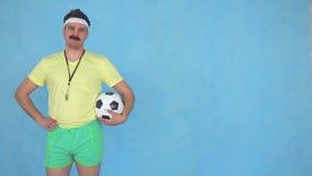 Hombre divertido con un coche del bigote con el balón de fútbol que presenta en la cámara metrajes