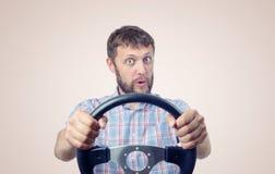 Hombre divertido con un volante, concepto de la impulsión del coche Imágenes de archivo libres de regalías