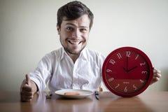 Hombre divertido de las marionetas con la camisa blanca que sostiene el reloj rojo Imagenes de archivo